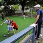 Family and children playing on artificial grass in the backyard